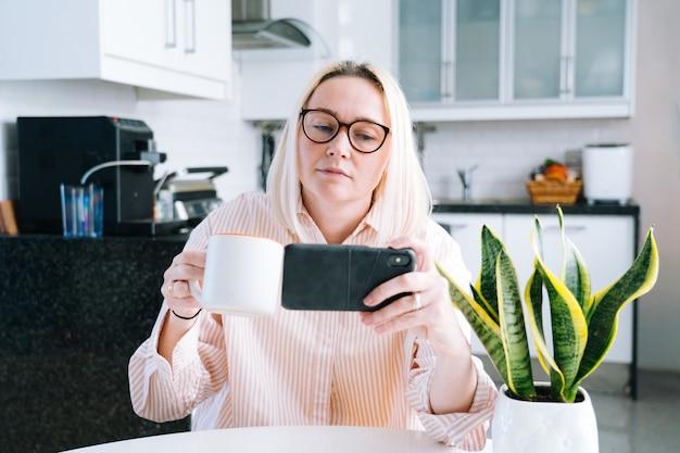 家庭の台所に座って、ビデオ通話を保持している幸せな女の子。友人や家族とのビデオ通話にスマートフォンを使用している若い女性。 vloggerの録画ウェビナー。カメラを探していると挨拶の手を振っている女性