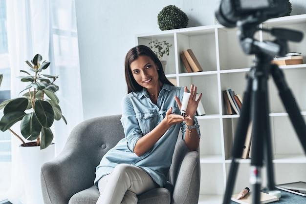 Vlogging。屋内で新しいビデオを作りながら美容製品を見せている魅力的な若い女性