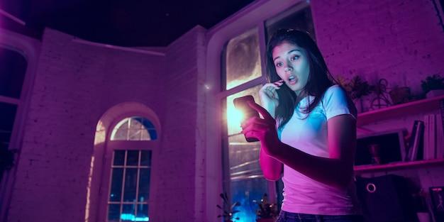 블로깅. 네온 조명이 켜진 실내에서 잘생긴 세련된 여성의 영화적 초상화. 보라색 - 파란색의 영화 효과처럼 톤. 실내에서 화려한 조명으로 스마트폰을 사용하는 백인 여성 모델. 전단.