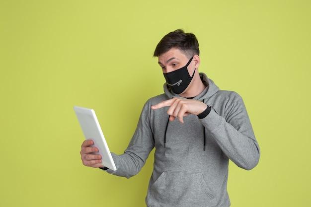 Vlogging、selfie。黄色のスタジオの壁に分離された白人男性の肖像画。黒のフェイスマスクの男性モデル。
