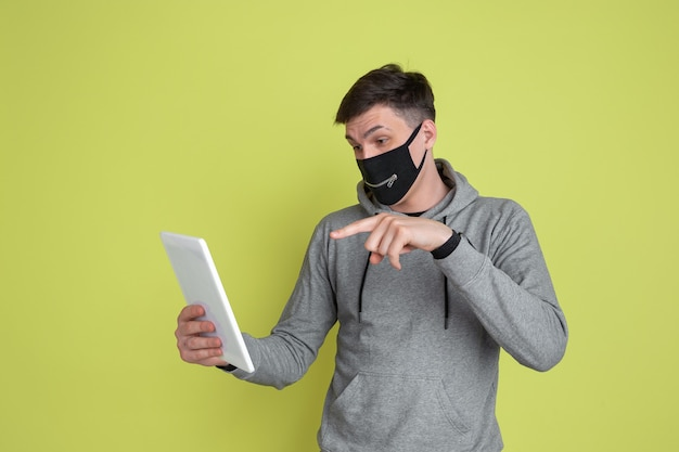 Vlogging, selfie. caucasian man's portrait isolated on yellow studio wall. male model in black face mask.