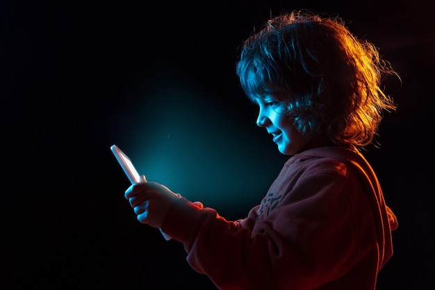 Vlogging with tablet, playing. caucasian boy's portrait on dark studio background in neon light. beautiful curly model. concept of human emotions, facial expression, sales, ad, modern tech, gadgets.