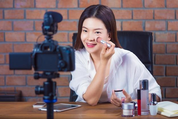 Молодая азиатская женщина онлайн косметический продавец vlogging, чтобы показать, как это сделать