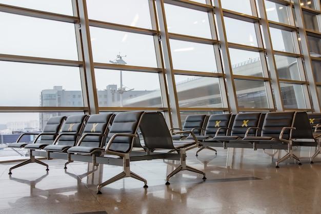 브누 코보 국제 공항, 출발 지역. 대유행 동안 사회적 거리를두기 위해 레이블이 붙은 대기 의자.