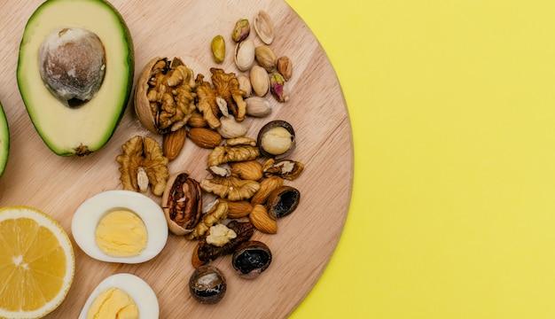 Яйца, авокадо, лимонные орехи на деревянной разделочной доске