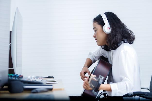 ボーカリストwearingheadphonesは、デジタルスタジオで曲を録音するギターを演奏します