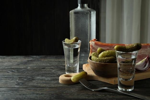 Водка и вкусные закуски на деревянном столе