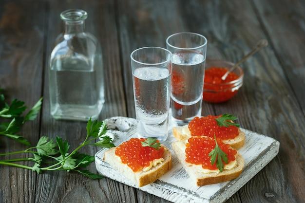 Водка и традиционные закуски на деревянных фоне