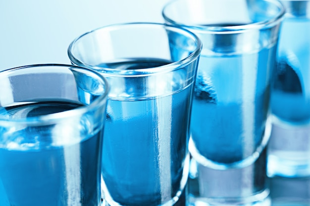 Vodka glass with ice on blue