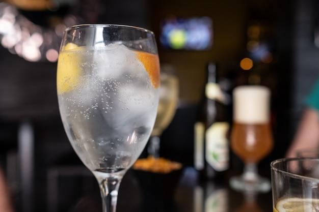 Vodka glass with lemon and orange slice in cocktail bar