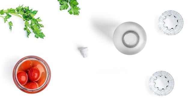 Водка, стаканы и соленые огурцы на белом фоне