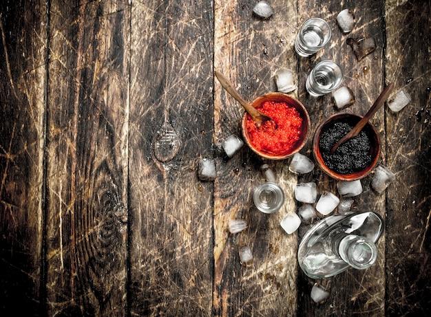 黒と赤のキャビアが入ったボトルに入ったウォッカ。木製の背景に。