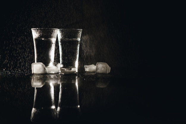Водка в рюмках на черном фоне, холодный крепкий напиток в запотевшем стакане