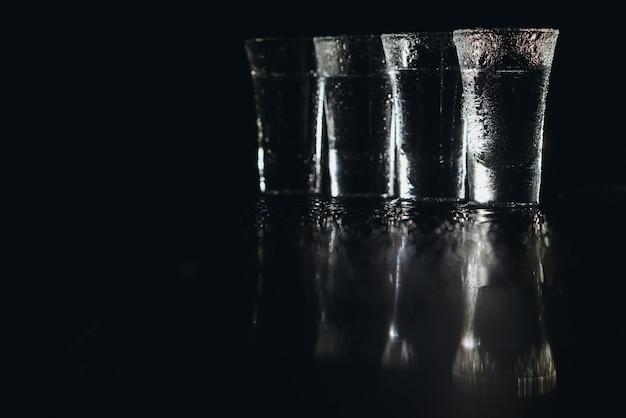 暗い背景のショットグラスのウォッカ。