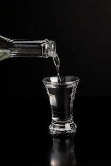 Vodka is poured from a bottle into a glass on a black table