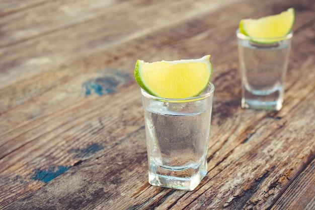 Vodka and lime slices on wood