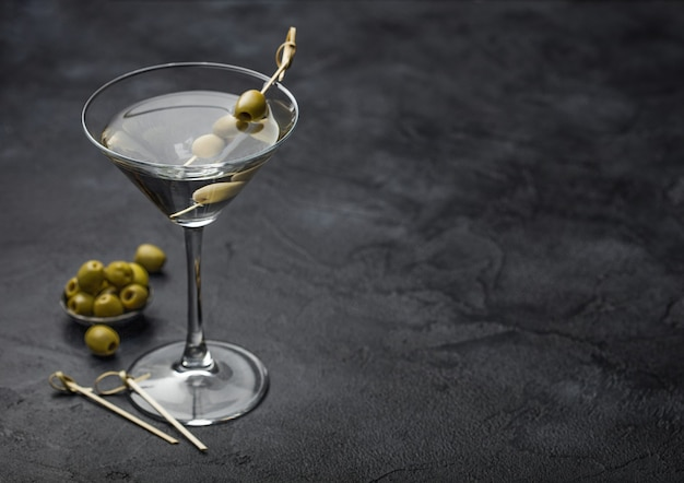 Vodka martini gin cocktail in original glass with olives in metal bowl and bamboo sticks on black surface.