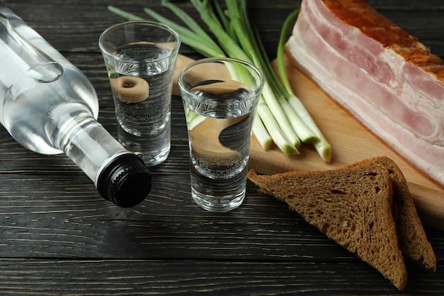 Водка, лук, бекон и хлеб на деревянных фоне