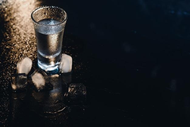 Водка. выстрелы, стаканы с водкой со льдом. темный фон. копировать пространство. выборочный фокус