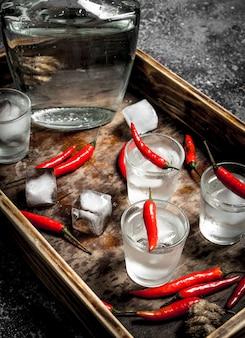 Рюмки водки с перцем чили на деревянном подносе на деревенском столе.