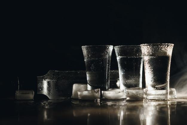 黒いテーブル、コピースペースに氷でウォッカショット