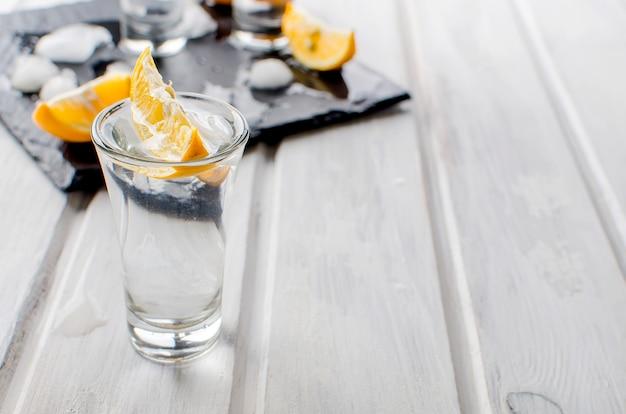 Vodka shots with lemon  on white table