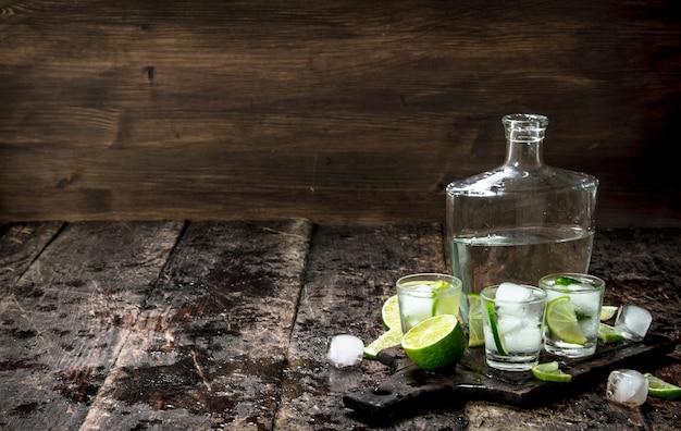 木製のテーブルの上のボードにライムと氷でウォッカショット。