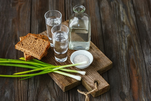 Vodka and traditional snack on wooden wall