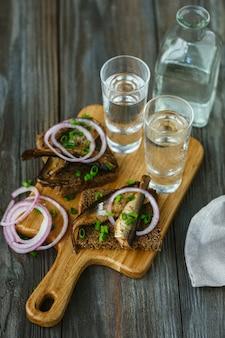 Vodka con pesce e pane tostato sulla parete in legno. bevanda alcolica pura artigianale e snack tradizionali. spazio negativo. celebrando il cibo e delizioso. vista dall'alto.