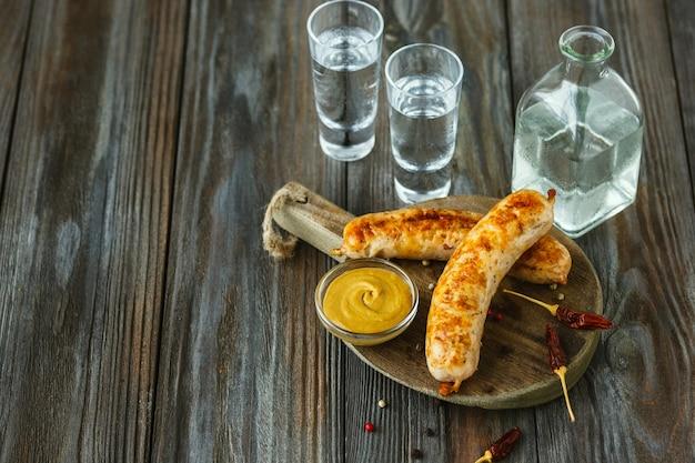 Vodka con salsicce fritte e salsa sul tavolo di legno