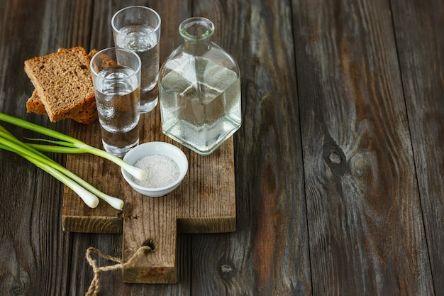 Vodka with green onion, bread toast and salt on wooden background. alcohol pure craft drink and traditional snack. negative space. celebrating food and delicious.