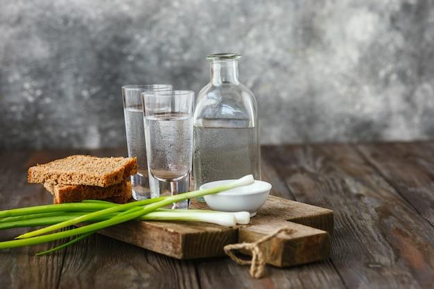 Vodka con cipolla verde, pane tostato e sale sulla tavola di legno