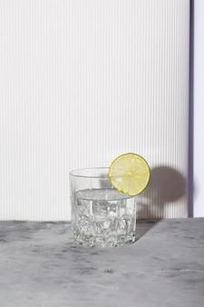 白い背景の上のガラスの氷とライムとウォッカ。トレンディな影と日光