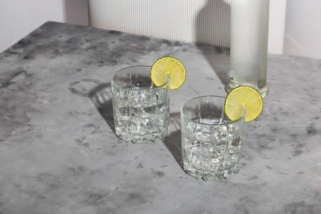 2杯のグラスとウォッカのボトルに氷とライムが入ったウォッカ。トレンディな影と日光