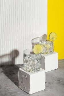 白いスタンドに2つのグラスに氷とライムのウォッカ。影と日光の流行