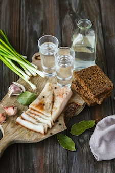 Vodka with lard and green onion on wooden table