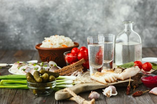 Водка с салом, соленой рыбой и овощами на деревянном столе