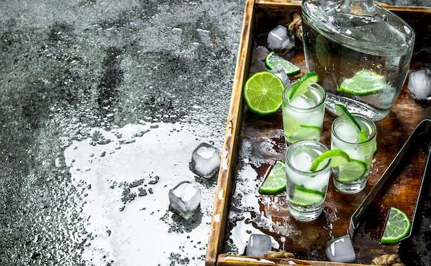 라임과 얼음 나무 쟁반에 보드카. 소박한 배경.