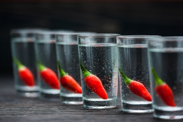 Vodka with  peppers on wooden table