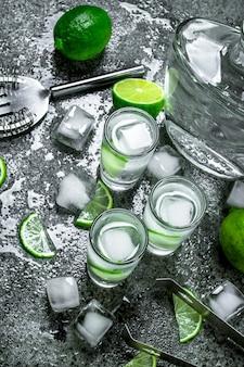 Водка с кусочками лайма и кубиками льда на деревенском столе