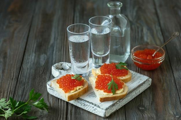 木製のテーブルにサーモンキャビアとパンのトーストとウォッカ