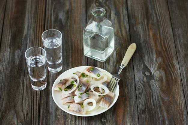 Водка с соленой селедкой и луком на деревянной поверхности. алкогольный чистый крафтовый напиток и традиционные закуски. негативное пространство. празднуем еду и вкусно.