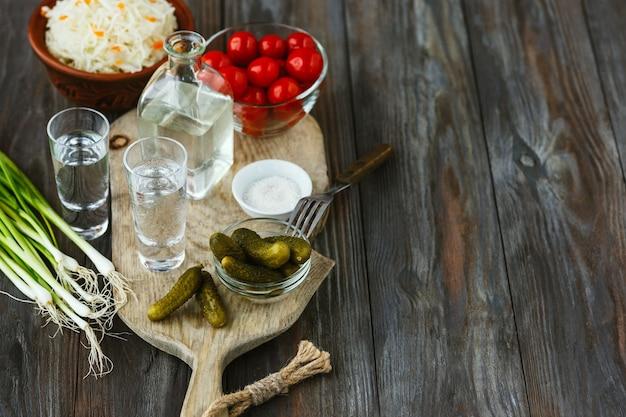 Водка с солеными овощами на деревянной поверхности. алкогольный чистый крафтовый напиток и традиционные закуски, помидоры, капуста, огурцы. негативное пространство. празднуем еду и вкусно.