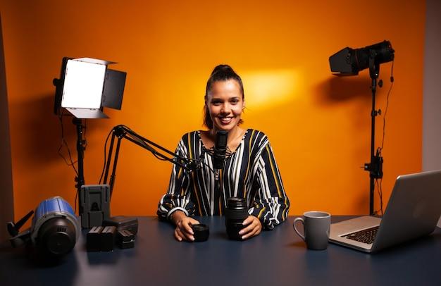 Voger smiling at camera while recording camera lens review