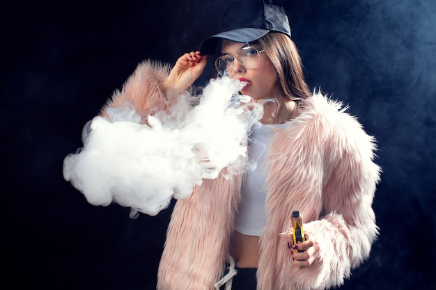 Vogue young woman puffing vapor