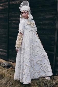 Девушка новой этнической русской моды vogue представляет креативную одежду возле старого дома, белое платье и шляпу, этническую одежду