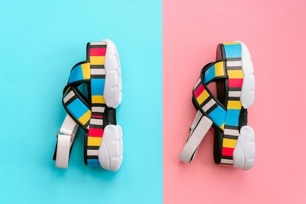Набор модной женской обуви. летние модные разноцветные женские сандалии на высоком танкетке на сине-розовой стене. voguish и стильная обувь для современных девушек.