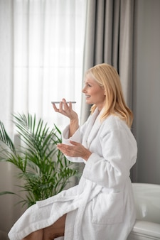 A voice message. a blonde woman recording a voice message and looking happy
