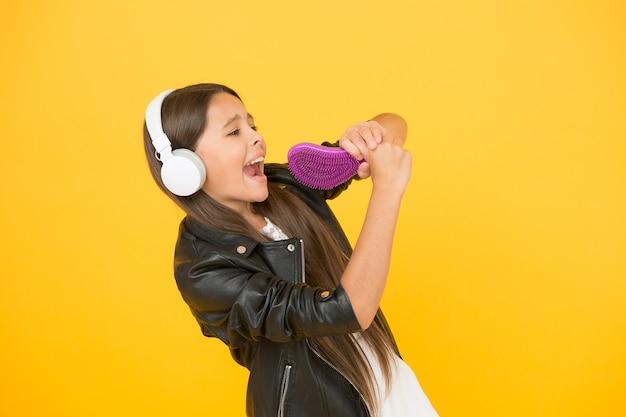 Синтез голоса изменит способ распространения музыки. наушники музыки маленькой девочки слушая. музыкальное образование. поющий микрофон для расчески. звукозаписывающая студия. красивый голос. развивающий голос.