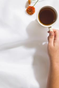 Взгляд сверху предпосылки ткани voile при женская рука держа кружку чая, 2 оранжевых цветка, с космосом для текста